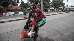 Pemudik membawa barang mereka seusai turun dari bus antarkota antarprovinsi (AKAP) di Terminal Kampung Rambutan, Jakarta, Minggu (23/5/2021). Hingga sore ini pemudik dari kota di Jawa Barat, Tengah, Timur, dan Sumatera terus berdatangan di Terminal Kampung Rambutan. (merdeka.com/Iqbal S Nugroho)