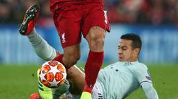 Gelandang Liverpool Roberto Firmino melewati pemain tengah Bayern Munchen Thiago Alcantara pada leg pertama babak 16 besar Liga Champions di Anfield, Liverpool, Inggris, Selasa (19/2). Pertandingan berakhir 0-0. (AP Photo/Dave Thompson)