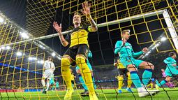 Pemain Borussia Dortmund Marco Reus memegang jaring gawang saat gagal mencetak gol melalui tendangan penalti ke gawang Barcelona pada laga Grup F Liga Champions di Dortmund, Jerman, Selasa (17/9/2019). Pertandingan berakhir 0-0. (AP Photo/Martin Meissner)