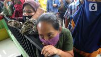 Warga menunggu giliran menerima uang Bantuan Sosial Tunai (BST) bulan Januari di halaman Masjid Jami Al-Hidayah RW 01 Bedahan, Depok, Selasa (16/2/2021). Sekitar 159.470 Keluarga Penerima Manfaat di Kota Depok menerima BST yang disalurkan PT Pos Indonesia pada Februari ini. (merdeka.com/Arie Basuki)