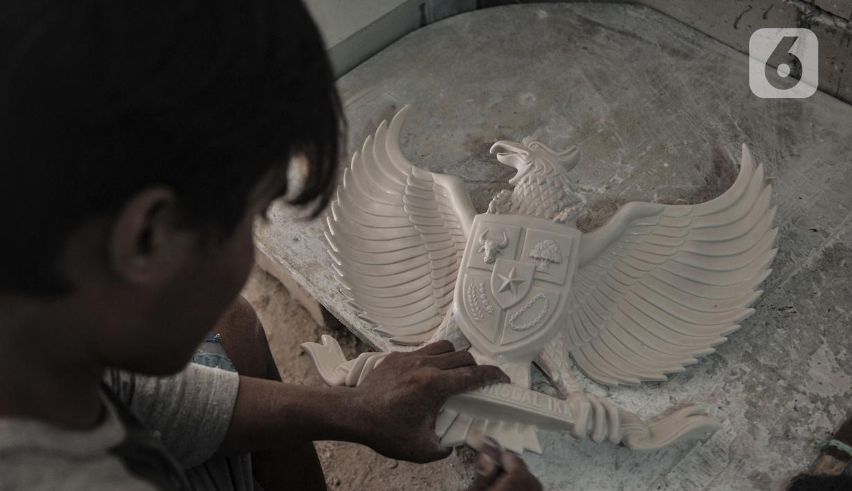 Perajin menyelesaikan pembuatan awal patung Garuda Pancasila di kawasan Jalan Bali Raya, Jakarta, Kamis (1/10/2020). Dampak Covid-19 menyebabkan produksi patung lambang negara Republik Indonesia tersebut menurun dan sempat tutup selama 3 bulan pada masa awal pandemi. (merdeka.com/Iqbal S. Nugroho)