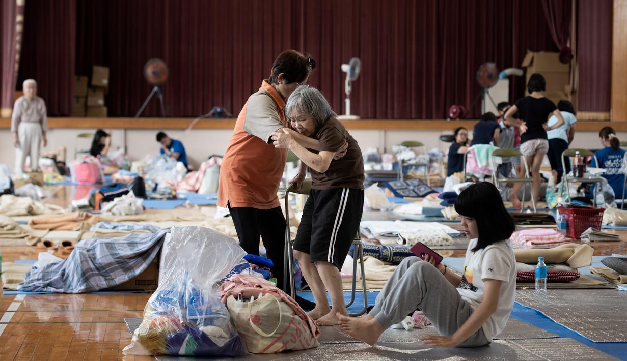 Pengungsi tua berusaha berdiri dari duduknya di lokasi pengungsian di Mabi, Prefektur Okayama, Jepang, Rabu (11/7). Pemerintah Jepang menyatakan banjir disertai tanah longsor telah menewaskan 179 orang. (Martin BUREAU/AFP)