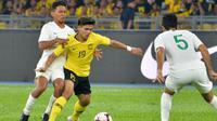 Pemain Timnas Indonesia, TM Ichsan dan Otavio Dutra, berusaha mengadang pemain Timnas Malaysia, Akhyar Rashid, dalam laga Grup G kualifikasi Piala Dunia 2022 di Stadion Nasional, Bukit Jalil (19/11/2019). (Bola.com/Dok. AFC)