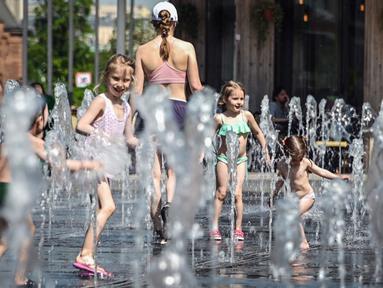 Orang-orang menikmati musim semi yang panas dengan mandi di air mancur di Moskow, Rusia, Selasa (18/5/2021). Suhu di Moskow telah mencapai 31 derajat Celcius. (Alexander NEMENOV/AFP)