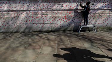 Anggota keluarga yang berduka melukis hati di Dinding Peringatan COVID-19 di seberang Gedung Parlemen Inggris, di London, Senin (29/3/2021). Mural hampir 150.000 lukisan hati tersebut untuk mengenang ribuan orang yang telah meninggal akibat virus corona di Inggris. (AP Photo/Kirsty Wigglesworth)