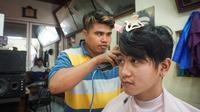Gibran Rakabuming Raka di sela blusukan menyempatkan untuk potong rambut di tukang cukur Madura.(Liputan6.com/Fajar Abrori)