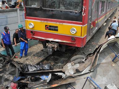Metromini B 80 jurusan Grogol-Kalideres tertabrak di pintu perlintasan sebelum Stasiun Angke, Tambora, Jakarta Barat, Minggu (12/6/2015). Saksi menyebut Metromini tersebut nekat menerobos pintu perlintasan.(Liputan6.com/Gempur M Surya)
