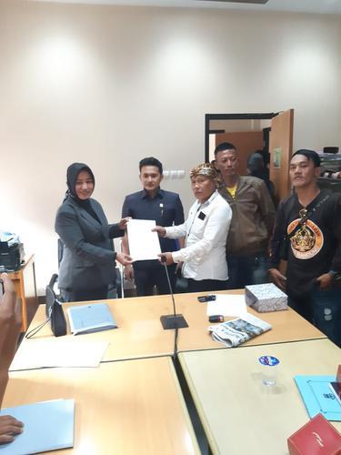 Kusna Kusdana, salah seorang calon kepala desa pemohon gugatan, tengah menerima berita acara penyerahan berkas gugatan saat audiensi ke DPRD Garut