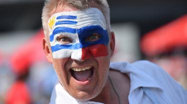 Seorang suporter mengecat wajahnya dengan bendera Uruguay dan Rusia jelang laga kedua negara dalam penyisihan Grup A Piala Dunia 2018 di Samara Arena, Samara, Rusia, Senin (25/6). (EMMANUEL DUNAND/AFP)