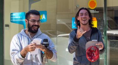 Dua pria tersenyum lebar setelah mendaftarkan diri sebagai konsumen ganja di kantor pos di Montevideo, Urugay, Selasa (2/5). Urugay menjadi yang pertama di dunia yang secara resmi melegalkan ganja untuk tujuan rekreasional. (Pablo PORCIUNCULA / AFP )