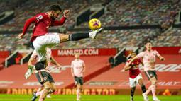 Gelandang Manchester United, Bruno Fernandes, menendang bola saat melawan Sheffield United pada laga Liga Inggris di Stadion Old Trafford,  Kamis (28/1/2021). MU takluk dengan  skor 1-2. (AP/Tim Keeton,Pool)