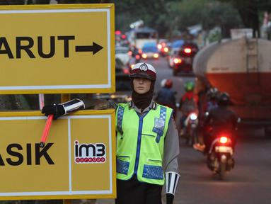 Papan penunjuk arah yang dipasang di Simpang Nagreg, Jawa Barat, Sabtu (2/7). Polisi memberlakukan sistem rekayasa lalu lintas untuk menghindari kemacetan yang menuju ke Garut dan Tasik. (Liputan6.com/Immanuel Antonius)