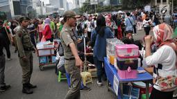 Satpol PP DKI Jakarta menertibkan PKL yang berdagang di kawasan Car Free Day, Bundaran HI, Jakarta, Minggu (20/1). Penertiban dilakukan karena telah membuat ketidaknyamanan bagi para pengunjung CFD yang ingin berolahraga. (Liputan6.com/Faizal Fanani)