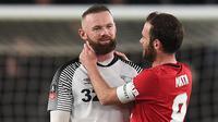Gelandang Manchester United, Juan Mata, berbincang dengan striker Derby Country, Wayne Rooney, pada laga babak kelima Piala FA di Pride Park Stadium, Kamis (5/3). Manchester United menang 3-0 atas Derby Country. (AFP/Oli Scarff)
