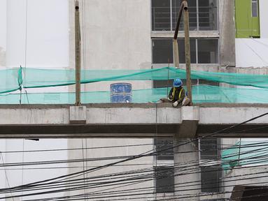 Pekerja menyelesaikan pembangunan JPO Pasar Rumput di Jakarta, Selasa (15/1). Pembangunan jembatan di bangunan pasar yang terintegrasi dengan rusun tersebut dibuat untuk memudahkan mobilitas warga. (Liputan6.com/Immanuel Antonius)
