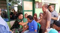 Kapten Inf Tatang Taryono, Komandan Koramil (Danramil) 2101/Sukaraja yang terjun langsung memberikan penanganan terapi gratis kepada masyrakat yang membutuhkan terapi saraf. (Dokpri)