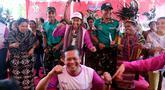 Menteri BUMN Rini Soemarno (tengah belakang) bersama Direktur ASABRI Sonny Widjaja (tengah depan) joget bersama masyarakat usai peresmian bantuan bedah rumah di Desa Oebelo, Kupang, Nusa Tenggara Timur (NTT), Selasa (14/8). (Liputan6.com/JohanTallo)
