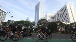 Pesepeda melintas Jalan Sudirman pada peluncuran jersey bersepeda Unlimited Hope hasil kokreasi Smartfren, Show The Monster dan Common Spot di Jakarta, Sabtu (27/3/2021). Hasil jersey bersepeda akan digunakan untuk pemberdayaan UMKM melalui Teman Kreasi Indonesia. (Liputan6.com/Pool)