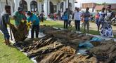 Warga melihat jenazah korban tsunami dan gempa 2004 di Kajhu, Aceh (19/12). Sekitar 30 jenazah korban tsunami Aceh dan gempa bumi ditemukan penduduk desa dekat lokasi konstruksi kompleks perumahan yang baru dibangun. (AFP Photo/Chaideer Mahyuddin)