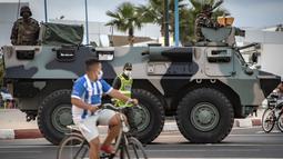 Seorang anak mengendarai sepeda saat tentara Maroko berpatroli di tengah wabah baru virus corona baru di kota Tangiers (11/8/2020). Tentara dikerahkan untuk meredam Lonjakan kasus Covid-19 di negara tersebut. (AFP/Fadel Senna)