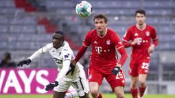 Penyerang Bayern Munchen, Thomas Mueller, berebut bola dengan pemain Hoffenheim, Diadie Samassekou, pada laga Bundesliga di Stadion Allianz Arena, Sabtu (30/1/2021). Bayern Munchen menang dengan skor 4-1. (Sven Hoppe/dpa via AP)