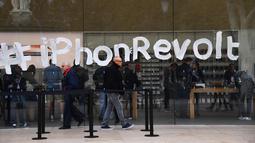 Warga melintasi jendela toko Apple yang ditulis oleh aktivis ATTAC saat unjuk rasa menentang penghindaran pajak oleh Apple saat peluncuran iPhone X di Aix-en- Provence, Prancis (3/11). (AFP Photo/Anne-Christine Poujoulat)