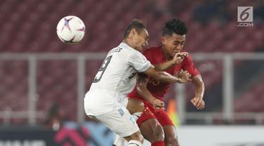 Pemain Timnas Indonesia, Febry Hariyadi (kanan) berebut bola dengan pemain Timor Leste pada laga penyisihan grup B Piala AFF 2018 di Stadion GBK, Jakarta, Selasa (13/11). Babak pertama berakhir imbang 0-0. (Liputan6.com/Helmi Fithriansyah)