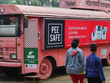 Foto pada 9 Februari 2020 menunjukkan orang-orang berjalan melewati toilet keliling di sebuah bus di taman umum di Pune, India. Proyek Ti Toilet, sebuah bus yang diubah menjadi toilet dan diluncurkan pada tahun 2016, adalah gagasan Ulka Sadalkar dan Rajeev Kheer. (Indranil MUKHERJEE/AFP)