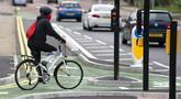 Seorang wanita mengendarai sepeda di jalur sepeda persimpangan CYCLOPS (Cycle Optimized Protected Signals) di wilayah selatan Manchester, Inggris (9/10/2020). Persimpangan CYCLOPS diluncurkan dengan desain unik yang memisahkan pejalan kaki dan pesepeda dari lalu lintas. (Xinhua/Jon Super)