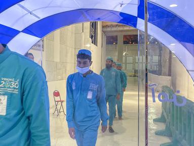 Para pekerja melewati gerbang sterilisasi mandiri yang didirikan di pintu masuk Ka'bah dan Masjid Haram selama bulan suci Ramadan di Mekkah pada 8 Mei 2020. Gerbang ini dipasang sebagai bagian dari tindakan pencegahan yang telah dilakukan sejak pecahnya Pandemi virus Corona (COVID-19). (STR / AFP)