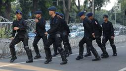 Personel Brimob menari bersama disela-sela berjaga di depan Gedung Mahkamah Konstitusi (MK), Jakarta, Selasa (25/6/2019). Kegiatan ini dilakukan untuk mengusir kejenuhan disela-sela pengamanan Gedung MK jelang sidang pembacaan putusan, Kamis (27/6). (Liputan6.com/Helmi Fithriansyah)