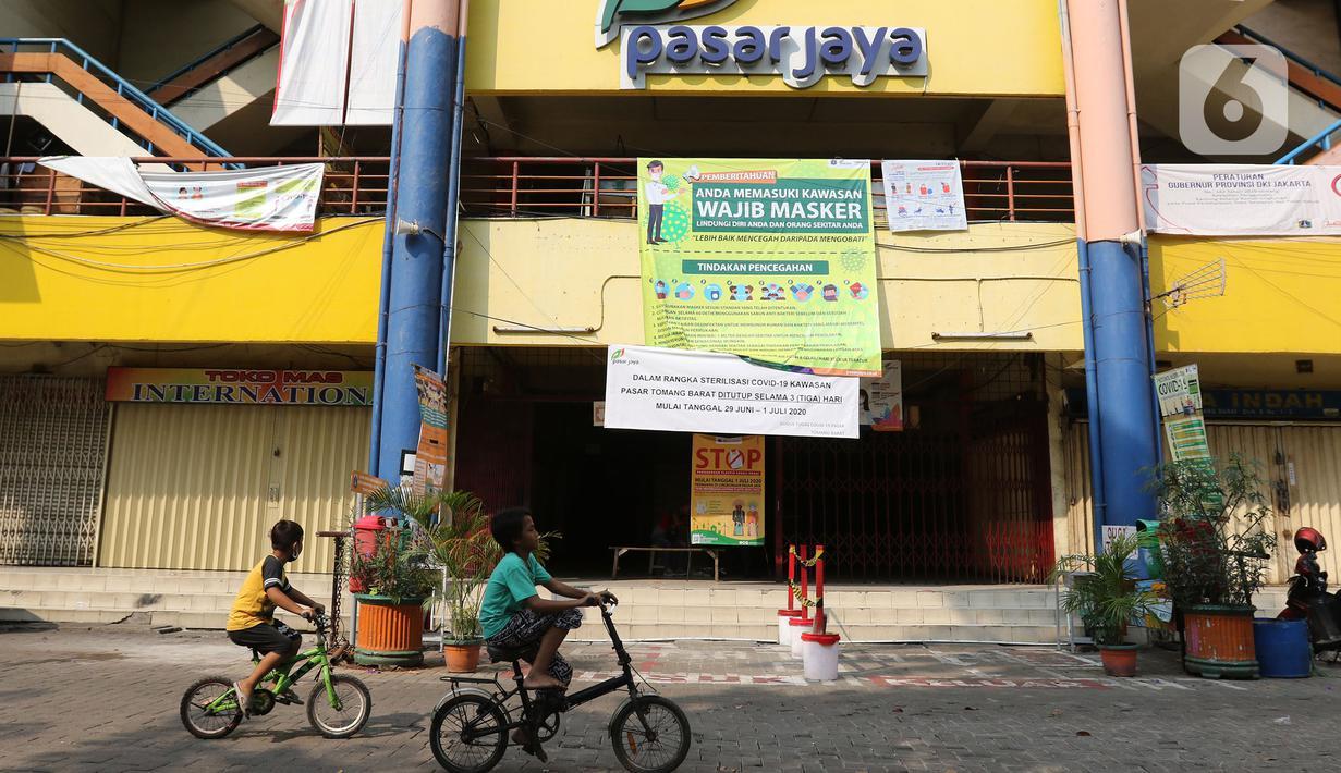 Anak-anak bermain sepeda di area Pasar Tomang Barat, Jakarta, Senin (29/06/2020). Pasar Tomang Barat atau yang lebih dikenal dengan sebutan Pasar Kopro itu ditutup mulai 29 Juni hingga 1 Juli setelah ada pedagang yang dinyatakan positif Covid-19 dari hasil tes usap. (Liputan6.com/Herman Zakharia)