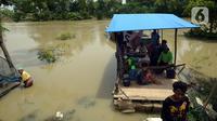 Warga menaiki perahu saat melintasi banjir di Desa Sindangsari, Kabupaten Bekasi, Jawa Barat, Rabu (24/2/2021). Sebagian rumah warga masih terendam banjir yang disebabkan jebolnya tanggul Sungai Citarum dan luapan Sungai Ciherang. (merdeka.com/Imam Buhori)
