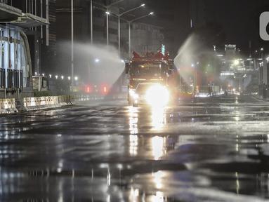 Petugas dari Dinas Penanggulan Kebakaran dan Penyelamatan DKI Jakarta menyemprotkan cairan disinfektan di sekitar Jalan Jenderal Sudirman-MH Thamrin, Jakarta, Kamis (31/12/2020). Jalan Jenderal Sudirman-MH Thamrin ditutup pada malam pergantian tahun 2020 menuju 2021. (Liputan6.com/Johan Tallo)