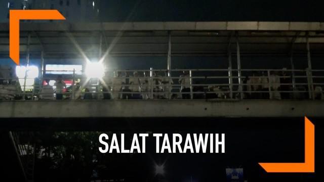 Warga Pasar Gembrong terpaksa melakukan ibadah Salat Tarawih di JPO karena lahan tidak tersedia.