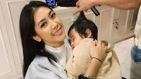 Aliya Rajasa Baskoro Yudhoyono saat menggendong putrinya yang tertidur saat potong rambut. (dok. Instagram @ruby_26/https://www.instagram.com/p/Bsmfol8giGq/Putu Elmira)