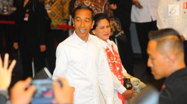 Capres 01 Joko Widodo atau Jokowi beserta istri Iriana Jokowi tiba di lokasi debat keempat Pilpres 2019 di Hotel Shangri-La, Jakarta, Sabtu (30/3). Debat kali ini mengangkat tema tentang ideologi, pemerintahan, pertahanan dan keamanan, serta hubungan internasional. (Liputan6.com/AnggaYuniar)