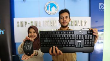 Dua siswa menunjukkan mouse dan keyboard Logitech di SMA Al-Azhar 2 Pejaten, Jakarta, Rabu (14/8/2019). Logitech berkomitmen untuk mendukung kemajuan eSport di Indonesia dengan memberikan peralatan gaming Logitech G dengan harapan mampu melahirkan atlet eSport yang berbakat. (Liputan6.com/HO/Ady)