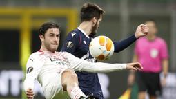 Bek AC Milan, Davide Calabria (kiri) berebut bola dengan gelandang Red Star Belgrade, Mirko Ivanic dalam laga leg kedua babak 32 Besar Liga Europa 2020/21 di San Siro Stadium, Kamis (25/2/2021). AC Milan bermain Imbang 1-1 dengan Red Star Belgrade. (AP/Antonio Calanni)