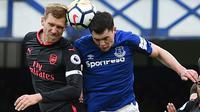 Bek Arsenal, Per Mertesacker (kiri) dan bek Everton, Michael Keane berebut bola pada matchday kesembilan Liga Primer Inggris di Goodison Park, Minggu (22/10). Bertandang ke markas Everton, Arsenal berhasil mengukir kemenangan telak 5-2. (Oli SCARFF / AFP)