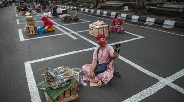 Pedagang menunggu pembeli di dalam garis petak-petak untuk menerapkan jaga jarak (physical distancing) di sepanjang jalan di Surabaya, Selasa (2/6/2020). Garis petak-petak bagi pedagang itu sebagai langkah pencegahan penyebaran COVID-19. (Photo by Juni Kriswanto / AFP)