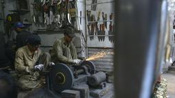 Pedagang membuat pisau untuk ritual pencambukan diri umat Syiah di sebuah toko di Pakistan (18/9). Hari Ashura menandai kesyahidan tujuh-abad cucu Nabi Muhammad, Imam Hussein yang tewas dalam pertempuran di Karbala, Irak 680 AD. (AFP Photo/Arif Ali)