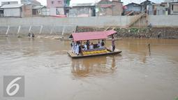 Para siswa SD saat berada di perahu eretan untuk berangkat ke sekolah di Sungai Ciliwung, Jakarta, Senin, (4/1). Usai libur panjang para siswa kembali beraktivitas mengikuti tahun ajaran 2016-2017. (Liputan6.com/Gempur M Surya)