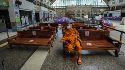 Seorang biksu Buddha mengenakan masker untuk membantu mengekang penyebaran COVID-19 duduk di bangku di Stasiun Kereta Api Hua Lamphong, Bangkok, Thailand, Selasa (20/7/2021). Dari 13.002 kasus COVID-19 terbaru di Thailand, sebanyak 11.953 kasus berasal dari masyarakat umum. (AP Photo/Sakchai Lalit)