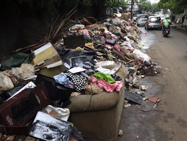 Tumpukan sampah terlihat menumpuk di sepanjang jalan pascabanjir mulai surut di kawasan Kembangan, Jakarta Barat, Minggu (5/1/2020). Pasca banjir yang melanda hampir di kawasan Jakarta mulai surut, tumpukan sampah terlihat di sepanjang jalan dari rumah-rumah warga. (Liputan6.com/Johan Tallo)