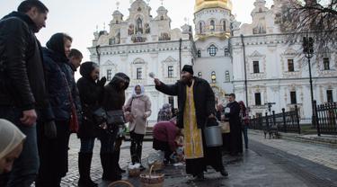 Imam Ortodoks Ukraina memberkati jemaatnya saat perayaan Paskah di gereja Kyiv-Pechersk Lavra di Kiev, Ukraina (8/4). Gereja Ortodoks Timur biasanya merayakan Paskah beberapa minggu setelah perayaan Paskah di gereja Barat. (AP Photo / Evgeniy Maloletka)