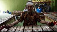 Rasino penyandang tuna netra yang menjadi guru gamelan di SMKN 8 Surakarta sedang memainkan instrumen gender.(Liputan6.com/Fajar Abrori)