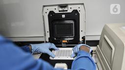 Tim medis memasukkan sampel ke dalam mesin PCR di laboratorium pemeriksaan Covid-19 di Labkesda DKI Jakarta, Selasa (4/8/2020). Labkesda DKI yang berjejaring dengan 47 lab se-Jakarta dalam sehari tercatat mampu menguji hampir 10.000 spesimen Covid-19 dengan metode PCR. (merdeka.com/Iqbal Nugroho)