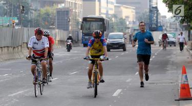 Warga berolahraga di kawasan Jalan Jenderal Sudirman hingga Jalan Thamrin, Jakarta, Minggu (17/6). Meski HBKB atau CFD ditiadakan, warga yang sudah terbiasa menjadikan lokasi ini untuk berolahraga tetap melakukan rutinitasnya. (Liputan6.com/Arya Manggala)