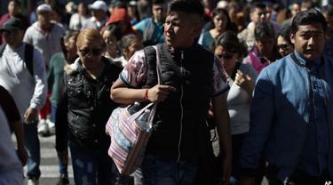 Seorang pria menggunakan tas kain untuk membawa belanjaannya di Mexico City, Rabu, 1 Januari 2020.